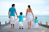 picture of family vacations  - Family of four on wooden jetty by the ocean - JPG