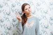 Young hipster woman doing v gesture and send kiss against wall indoor
