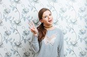 Young hipster woman doing v gesture against wall indoor