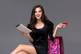 stock photo of packages  - Beautiful young girl paying by credit card for shopping with a laptop and packages against gray background - JPG