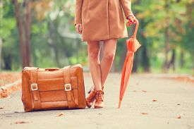 picture of grils  - Gril in coat with umbrella and suitcase in the park - JPG