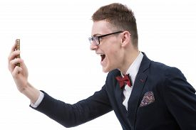 stock photo of angry  - Angry business man screaming on cell mobile phone portrait of young handsome businessman isolated over white background - JPG