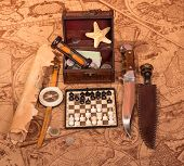 stock photo of treasure map  - Old compass lying on antique map with treasure chest - JPG