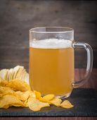 image of potato chips  - Beer with foam in glass mug and potato chips on wooden table - JPG
