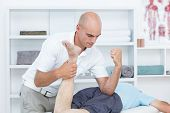 picture of physiotherapist  - Physiotherapist doing leg massage to his patient in medical office - JPG