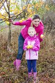 stock photo of leggins  - Mother and her daughter with autumnal apple tree holding an apples - JPG