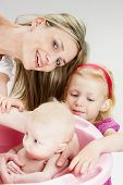 image of bathing  - portrait of mother with her baby and daughter during bathing - JPG