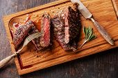 stock photo of ribeye steak  - Sliced medium rare grilled Beef steak Ribeye with rosemary on cutting board on wooden background - JPG