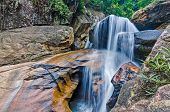 stock photo of jungle  - Beautiful photo of waterfalls with soft flowing water and large colored rocks - JPG