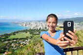 foto of waikiki  - Hawaii tourist taking selfie photo of Honolulu and Waikiki beach using smartphone - JPG
