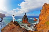 image of arid  -  The woman ashore in a white suit for yoga carries out a pose  - JPG