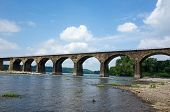 picture of old bridge  - One hundred year old stone arch railroad bridge stretching over a river - JPG
