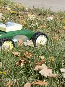 picture of tallgrass  - green and yellow toy lawn mower sitting in tall green grass with brown leaves - JPG