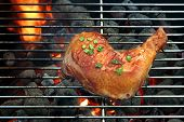 image of flame-grilled  - Grilled Glazed Chicken Quarter On The Hot BBQ Charcoal Flaming Grill Close - JPG