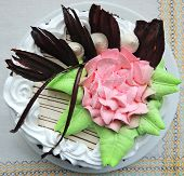 picture of sponge-cake  - Delicious sponge cake with pink cream flower and chocolate decorations on a plate on a white linen napkin - JPG