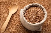 pic of buckwheat  - Full linen sack with buckwheat on background of scattered buckwheat with wooden spoon - JPG