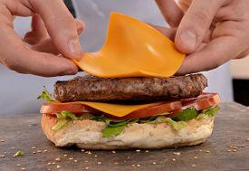 image of burger  - Cook preparing cheese burger - JPG