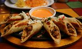 picture of mexican food  - a mexican dish of rolled crilled chicken tacos with a chipotle cheese sauce - JPG