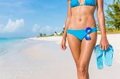 Sexy bikini body woman - abs, sunglasses, flip flops on beach vacation. Model showing slim abs and t poster