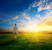 Постер, плакат: один человек и поле весеннего трава и закат