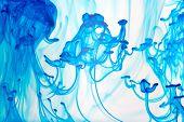 Líquido azul en agua haciendo formas abstractas