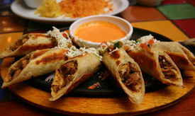 stock photo of mexican food  - a mexican dish of rolled crilled chicken tacos with a chipotle cheese sauce - JPG