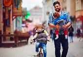 Happy Father And Two Sons On The City Walk. Parental Leave. Baby Carrier poster