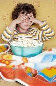 foto of televisor  - Kid watching a scary movie eating pop corn - JPG