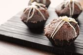 Tasty chocolate cupcakes on wooden board poster