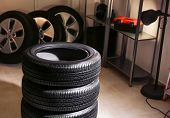 Car tires in automobile service center poster