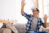 Relaxing At Weekend. Cheerful Well-built Stylish Adolescent Wearing A Vr Headset And Relaxing While  poster