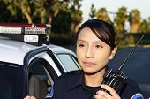 stock photo of lightbar  - a Hispanic police officer holding her radio - JPG