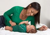 pic of happy baby boy  - Biracial mom on bed with her multiethnic black infant son  - JPG