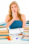 Shocked Teen Girl Sitting At Desk With Piles Of Books