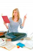 Pensive Teenager Sitting On Floor Among Schoolbooks And Studying poster