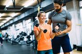 Young Beautiful Woman Doing Exercises With Personal Trainer In Gym poster