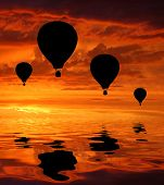 Silhouettes of four hot air balloons in sunrise