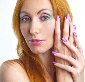 Portrait of the young woman with a make-up in pink tones and with long nails