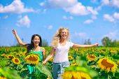 Spring happy women running through nature field of sunflowers in outdoor summertime fun. Girlfriends poster
