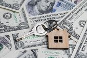 Saving Money For House Or Mortgage Loan Concept, Key With Wooden House Key Chain On Pile Of Us Dallo poster