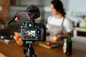 Female vlogger recording cooking related broadcast at home poster