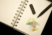 Detail Of  A Notepad With Pencil And Paperclips