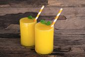 Mango Smoothies Juice And Ripe Mango Fruits. Yellow Fruit On Old Wooden Floor, Drink In The Morning  poster