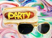 Hot Dog in bun with the word PARTY in yellow mustard and  Sunglasses on a Psychedelic Pattern Backgr poster