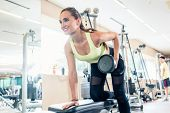Low-angle view portrait of a beautiful fit woman smiling while exercising one arm dumbbell row for b poster