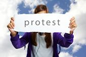 Image of teenage girl in casual clothes expressing protest with sheet of paper