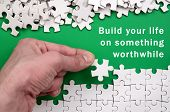 Build Your Life On Something Worthwhile. The Hand Folds A White Jigsaw Puzzle And A Pile Of Uncombed poster