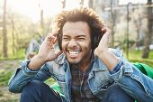 Постер, плакат: Close up Outdoor Portrait Of Handsome African Man With Afro Haircut Holding Hands On Headphones Whil