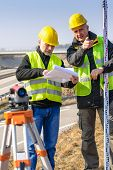 Land surveyors on highway reading geodesist plans use tacheometer