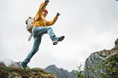 Adventure Tourist Jumping On Rocks Over Cliff. Brave Man Traveler Hiking Trail In Authentic Wilderne poster